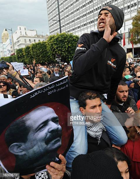 A Tunisian protester shouts slogans near a poster featuring killed opposition leader Chokri Belaid during a demonstration on February 23 2013 on the...