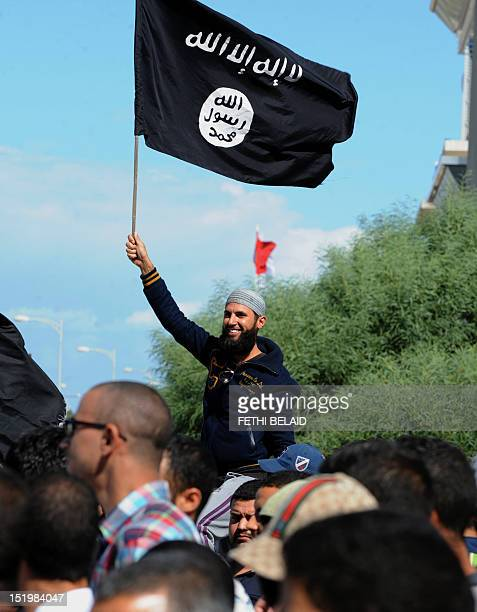 A Tunisian protester waves an AlQaeda affiliated flag during a protest outside the US embassy in Tunis on September 14 2012 against a film mocking...
