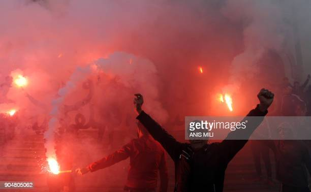 Tunisian protesters carry flares and shout slogans during celebrations in central Tunis on January 14 marking the seventh anniversary since the...