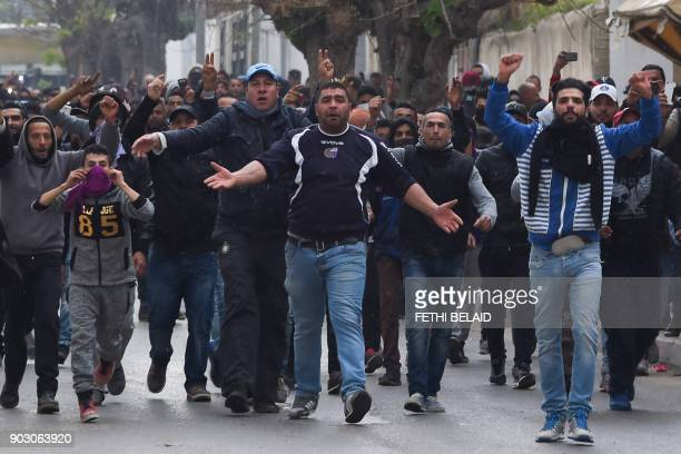 TOPSHOT Tunisian protesters gesture towards security forces during clashes in the town of Tebourba on January 9 following the funeral of a man who...