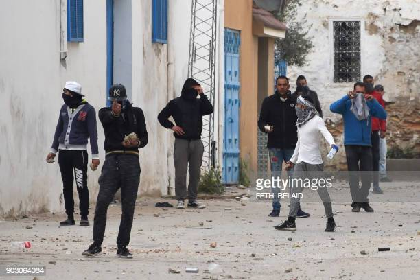 Tunisian protesters gesture towards security forces during clashes in the town of Tebourba on January 9 following the funeral of a man who was killed...
