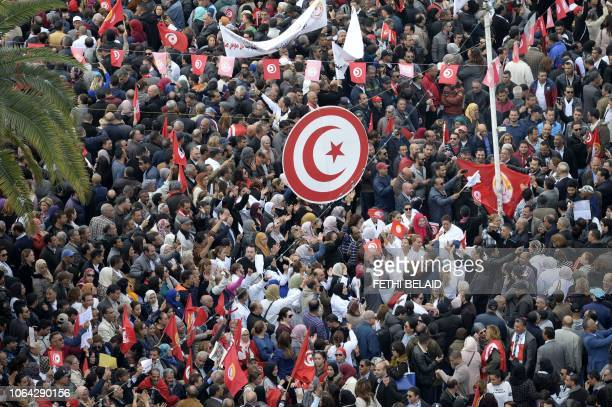 Tunisian protesters wave national flags and chant slogans during a civil servants general strike after the failure of negotiations with the...