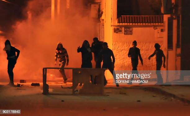Tunisian protestors throw stones towards security forces in Tunis' Djebel Lahmer district early on January 10 2018 after price hikes ignited protests...