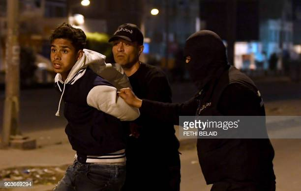 TOPSHOT Tunisian security forces detain a protester in the Ettadhamen on the outskirts of Tunis late on January 10 after price hikes ignited protests...