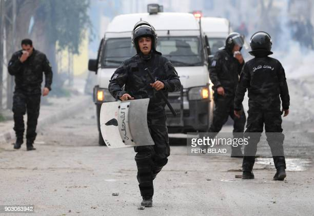 Tunisian security forces stand amid tear gas during clashes with protesters in the town of Tebourba on January 9 following the funeral of a man who...