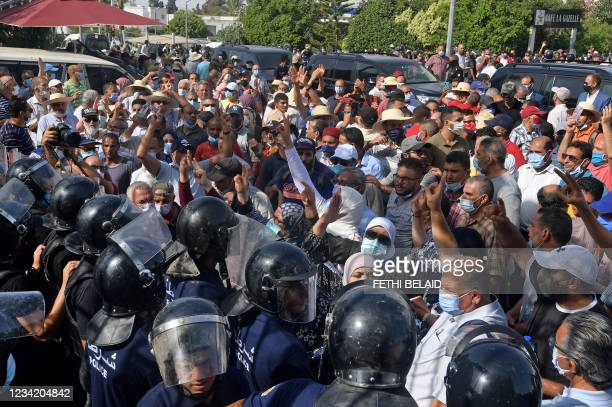 Tunisian security officers hold back protesters outside the parliament building in the capital Tunis on July 26 following a move by the president to...