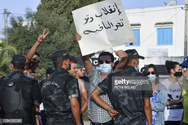 Tunisian security officers intervene as supporters of President Kais Saied chant slogans denouncing the country's main Islamist Ennahda party in...
