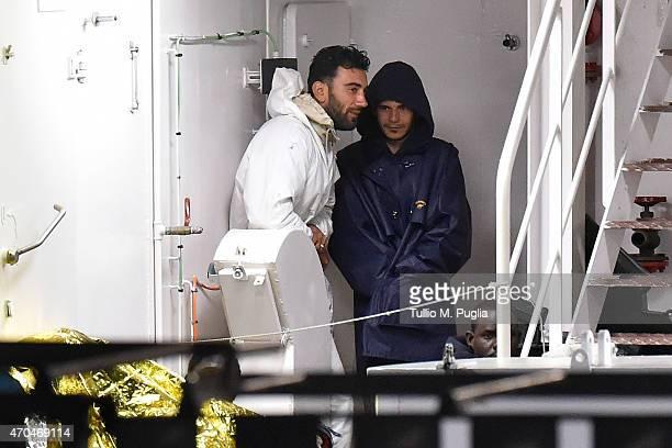 Tunisian skipper Mohammed Ali Malek and Syrian crew member Mahmud Bikhit stand on the deck of the Italian Coast Guard ship Gregretti which is...