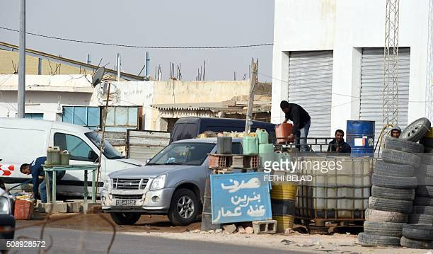 Tunisian smugglers unload barrels of oil that they illegally imported from Libya to Tunisia before selling them on a road on February 6 2016 in Ben...