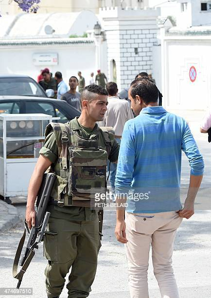 A Tunisian soldier checks people outside the Bouchoucha army barracks in Tunis on May 25 2015 after a soldier opened fire at his colleagues A...