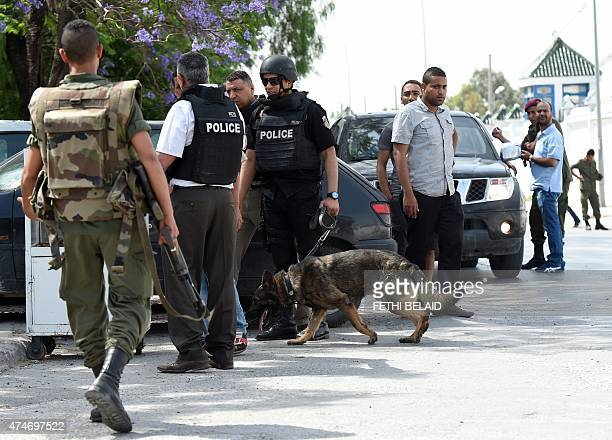 Tunisian soldiers and policemen stand guard outside the Bouchoucha army barracks in Tunis on May 25 2015 after a soldier opened fire at his...