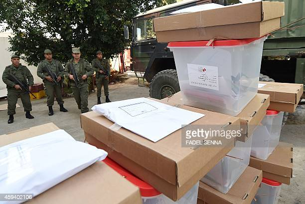 Tunisian soldiers stand guard as election commission workers unload ballot boxes from a military truck at a polling station in the city of Beja on...