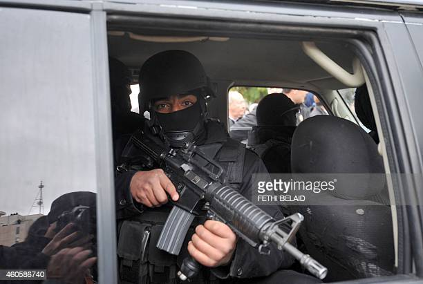 Tunisian special forces stand guard in a vehicle as Tunisian presidential candidate and former prime minister Beji Caid Essebsi gives a speech during...