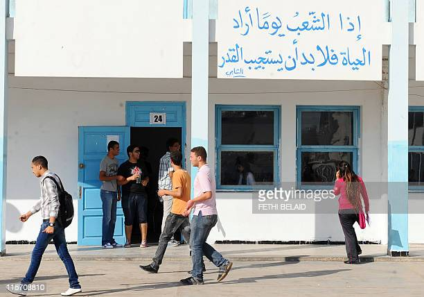 """Tunisian students prepare to take the baccalaureat exam on June 9, 2011 in Tunis. Arabic script translates as """"when one day, the people hoped to..."""