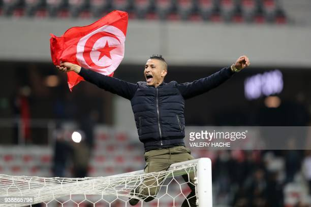 A Tunisian supporter holding a flag of Tunisia sits on a goal post celebrates after his team won 10 at the end of of the international friendly...