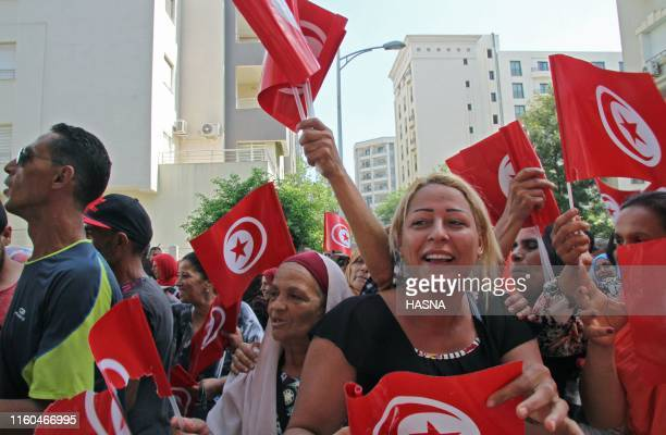 Tunisian supporters of the Tahya Tunis political party wave the national flag in Tunis on August 9 after the Prime Minister submitted his candidacy...