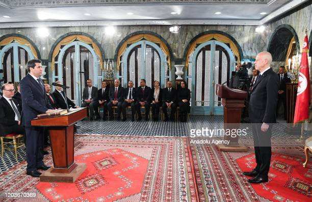 Tunisian Transport and Logistics Minister Anwar Maarouf puts his hand on the Quran during sworn in ceremony of new cabinet in Tunis Tunisia on...