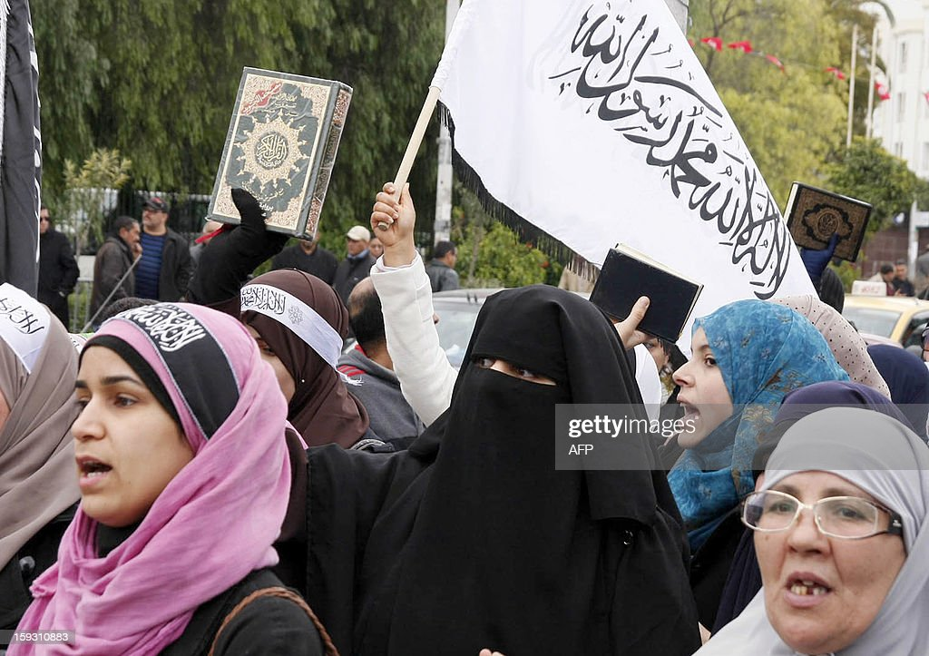Tunisian veiled women hold a Koran and a flag reading 'There's no God but God and Mohammed is his prophet' during a demonstration of the Tunisian Islamist party Hizb Ettahrir outside the National Constituent Assembly to demand the application of the Islamic sharia law on January 11, 2013 in Tunis.