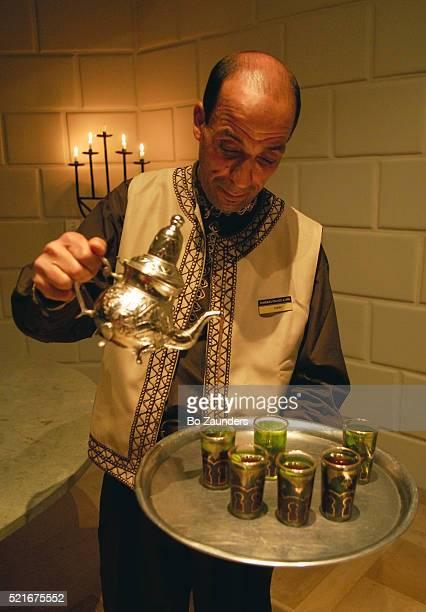tunisian waiter pouring tea - bo zaunders stock pictures, royalty-free photos & images