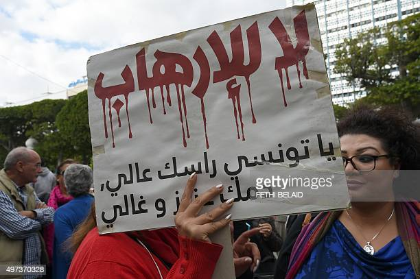 """Tunisian woman carries a placard, which reads in Arabic """"No to terrorism"""" during a silent march in Habib Bourguiba Avenue in Tunis on November 16,..."""