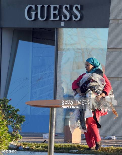 A Tunisian woman carrying clothes in her hand walks past a looted supermarket on January 15 2011 in La Gazella city near Tunis Tunisia's speaker of...