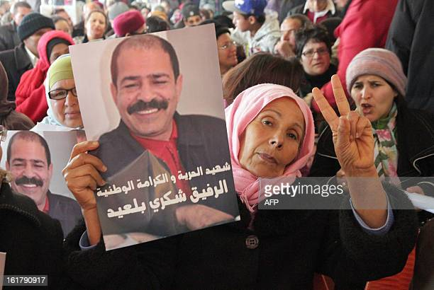 A Tunisian woman flashes the sign of victory holding a portrait of murdered opposition figure Chokri Belaid during a meeting in his memory with his...