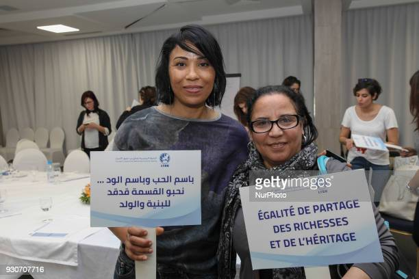 A Tunisian woman holds a placard which reads in arabic 'In the name of love and in the name of roses we want equality in the inheritance between the...