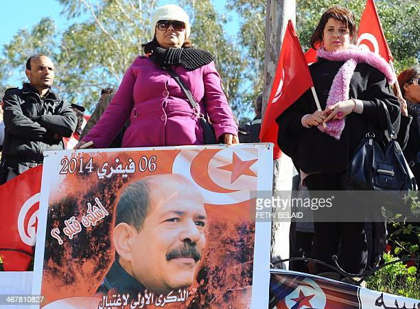 A Tunisian woman holds a placard with a portrait of murdered opposition figure Chokri Belaid outside ElJellaz cemetery in a suburb of Tunis where...
