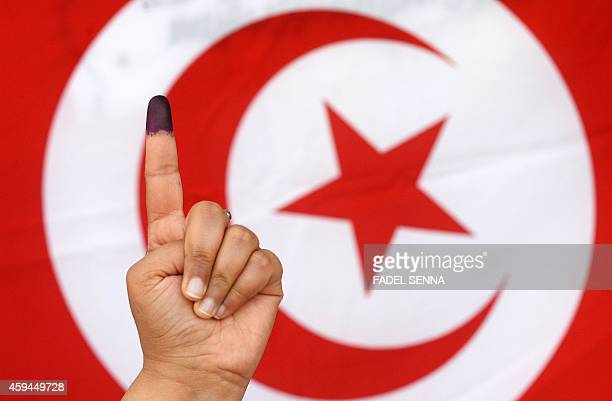 A Tunisian woman raises her inkstained finger in front of a national flag after casting her vote in the country's first postrevolution presidential...