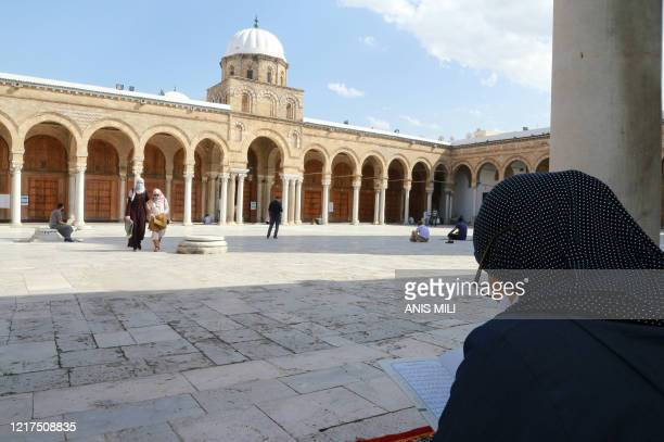 Tunisian woman reads the Koran in the court of Al-Zaytuna mosque, the oldest in the capital Tunis, on June 4 following its reopening after...