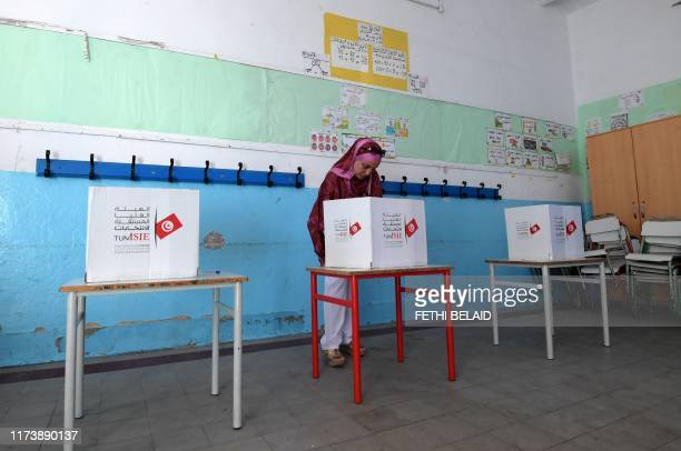 Tunisian woman stands behind a voting booth at a polling station in the capital Tunis on October 6 during the third round of legislative elections...