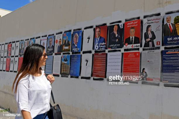A Tunisian woman walks in front of posters of presidential candidates in the capital Tunis on September 7 2019 Tunisia has long been seen as a...
