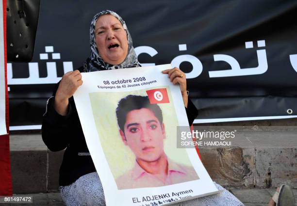 A Tunisian woman who had lost her son in the Mediterranean sea as he attempted to cross into Europe by boat carries his portrait during a...