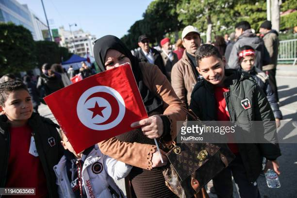 A Tunisian woman with her kids hold he flag of Tunisia as they attend the celebrations of the 9th held on avenue Habib Bouguiba in the capital Tunis...