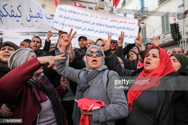 Tunisian women and men make the victory sign while raising placards and shooting slogans as they attend a gathering held outside the UGTT labor union...