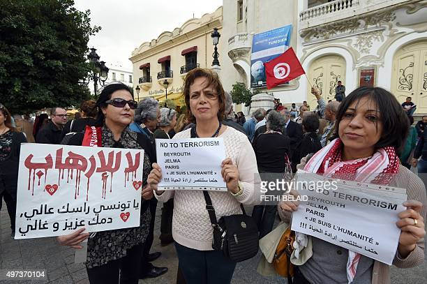 Tunisian women carry placards during a silent march in Habib Bourguiba Avenue in Tunis on November 16, 2015 for the victims the attacks in the French...