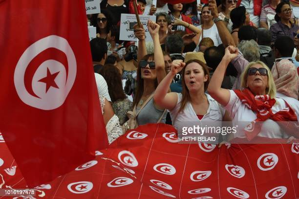 Tunisian women chant slogans and wave their national flags during a demonstration to mark Tunisia's Women's Day and to demand equal inheritance...