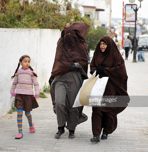 Tunisian women one wearing a burka walk in the empty Hammamet centre as thousands of Tunisian tour operators and residents of tourist town of...