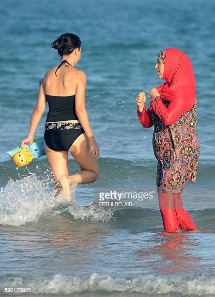 Tunisian women one wearing a burkini a fullbody swimsuit designed for Muslim women walk in the water on August 16 2016 at Ghar El Melh beach near...