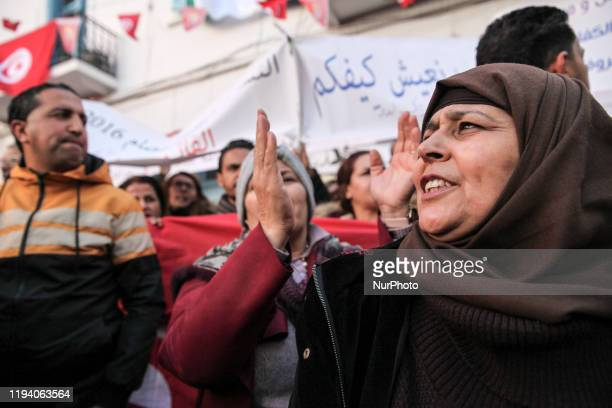 Tunisian women shoot slogans as they attend a gathering held outside the UGTT labor union headquarters in Tunis to celebrate the 9th anniversary of...