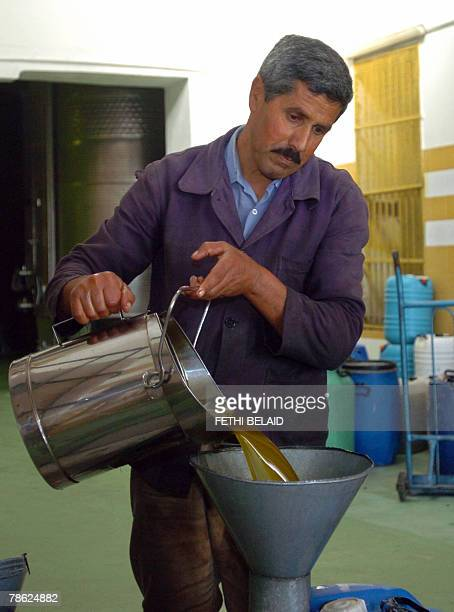 A Tunisian worker pours olive oil during the fabrication of olive oil 22 December 2007 in Sabbalet Ammar near Tunis 5 percent of the world olive...