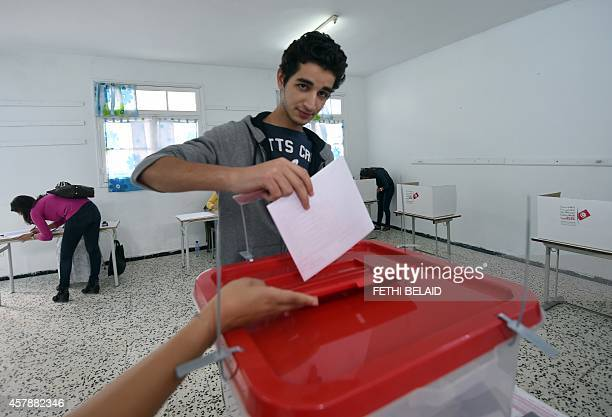 A Tunisian young man casts his vote in the country's first postrevolution parliamentary election on October 26 2014 at ElManzeh VI School turned into...