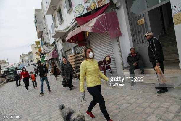Tunisian young woman wearing a face mask to prevent the coronavirus COVID-19 walks with her dog among people on the street in Ariana city, Northern...