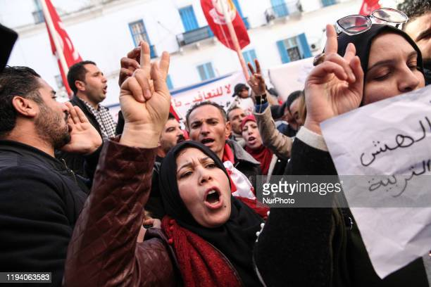 Tunisian young women and men make the victory sign while shooting slogans as they attend a gathering held outside the UGTT labor union headquarters...