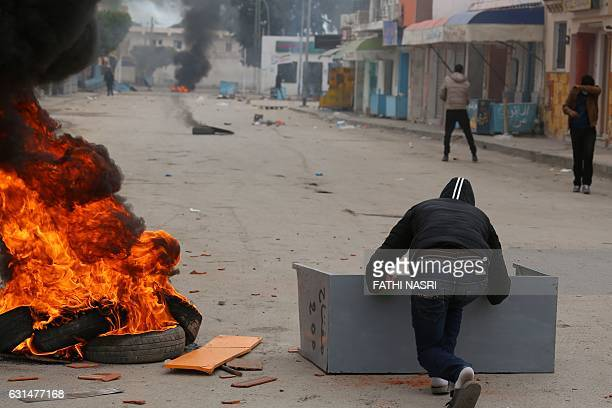 Tunisian youths throw stones towards the police station during a demonstration on January 11 2017 in the Tunisian southern border town of Ben...