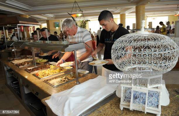 Tunisians and tourists serve themselves from a buffet at the Sidi Mansour restaurant in Djerba on August 1 2010 AFP PHOTO / FETHI BELAID / AFP PHOTO...