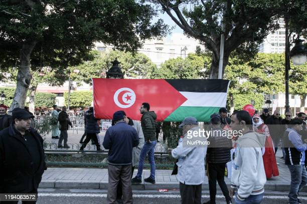 Tunisians are seen next to a giant flag of Palestine and Tunisia set up on avenue Habib Bouguiba in the capital Tunis during the celebrations of the...