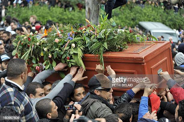 Tunisians carry the coffin of assassinated opposition leader Chokri Belaid ahead of his burial at ElJellaz cemetery in a suburb of Tunis on February...