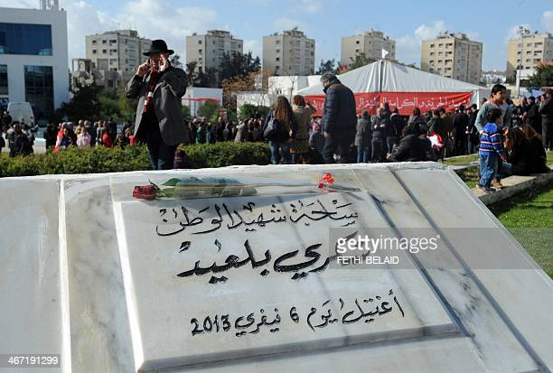 Tunisians gather near a memorial for slain opposition leader Chokri Belaid at a newly inaugurated square bearing his name to commemorate the first...