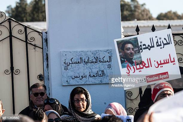 Tunisians hold placards during a demonstration in demand release of writer Yassine Ayari who is judged by military tribunals in the capital Tunis...